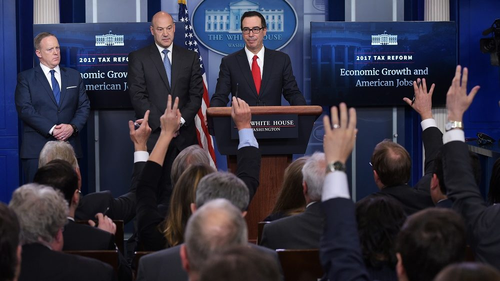 Reporters raise their hands with questions for Treasury Secretary Steven Mnuchin (R) and Chief Economic Advisor Gary Cohn (L) watched by White House Press Secretary Sean Spicer in the Brady Briefing Room on US President Donald Trump's tax reform plans on April 26, 2017 in Washington, DC. / AFP PHOTO / MANDEL NGAN