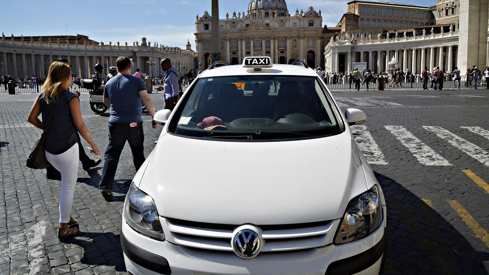 """People walk nexto to a Volkswagen taxi in St Peter Square, in the Vatican city in Rome, on September 22, 2015. The Italian transport ministry said Tuesday it will open an inquiry over the Volkswagen emissions scandal and demand explanations from the German auto giant. The ministry said in a statement it was """"concerned"""" about the matter and it was """"launching an inquiry into the manufacturer"""". The move followed the revelations in the United States that Volkswagen had equipped diesel cars with a device that can cheat pollution tests. Italy said it needs to know if any such cars were sold in Italy. AFP PHOTO / ANDREAS SOLARO / AFP PHOTO / ANDREAS SOLARO"""
