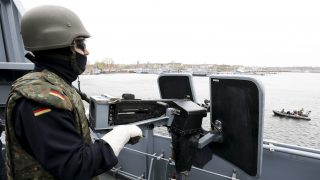 A soldier of the Einsatzflottille 1 (lt. Operation Flotilla) on a machine gun on the deck of the Alster corvette at the naval base in Kiel, Germany, 21 April 2017. German defence minister von der Leyen visited the naval base in Kiel on Friday and got an impression of the tasks and abilities of the units of the Einsatzflotille 1. Photo: Christian Charisius/dpa