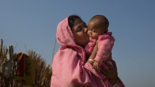 """A Rohingya mother kisses her new born baby at Kutupalong Refugee Camp, Cox's Bazar, Bangladesh on February 13, 2017.. After attacks by Rohingya militants on border police posts on October 9, 2016, the Burmese military undertook a series of """"clearance operations"""" in northern Rakhine State. Security forces summarily executed men, women, and children; looted property; and burned down at least 1,500 homes and other buildings. More than 69,000 Rohingya fled to Bangladesh. Currently the number is more than 70,000. (Photo by Turjoy Chowdhury/NurPhoto)"""