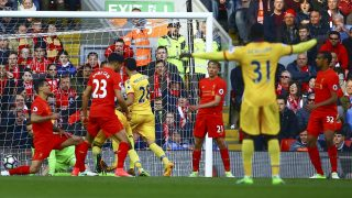 Crystal Palace's Zaire-born Belgian striker Christian Benteke (obscured) scores past Liverpool's Belgian goalkeeper Simon Mignolet (L) during the English Premier League football match between Liverpool and Crystal Palace at Anfield in Liverpool, north west England on April 23, 2017. / AFP PHOTO / Geoff CADDICK / RESTRICTED TO EDITORIAL USE. No use with unauthorized audio, video, data, fixture lists, club/league logos or 'live' services. Online in-match use limited to 75 images, no video emulation. No use in betting, games or single club/league/player publications.  /