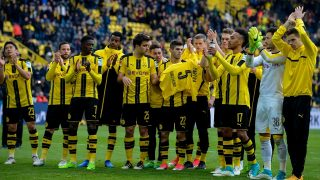 The team of Borussia Dortmund celebrates the win after the final whistle with the shirt of their missing Dortmund's Spanish defender Marc Bartra who was injured during the bus attack after the the German First division Bundesliga football match between Borussia Dortmund and Eintracht Frankfurt, in Dortmund, western Germany, on April 15, 2017.  / AFP PHOTO / SASCHA SCHUERMANN / RESTRICTIONS: DURING MATCH TIME: DFL RULES TO LIMIT THE ONLINE USAGE TO 15 PICTURES PER MATCH AND FORBID IMAGE SEQUENCES TO SIMULATE VIDEO. == RESTRICTED TO EDITORIAL USE == FOR FURTHER QUERIES PLEASE CONTACT DFL DIRECTLY AT + 49 69 650050