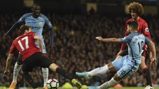 Manchester City's Argentinian striker Sergio Aguero (R) shoots but has his shot saved during the English Premier League football match between Manchester City and Manchester United at the Etihad Stadium in Manchester, north west England, on April 27, 2017. / AFP PHOTO / PAUL ELLIS / RESTRICTED TO EDITORIAL USE. No use with unauthorized audio, video, data, fixture lists, club/league logos or 'live' services. Online in-match use limited to 75 images, no video emulation. No use in betting, games or single club/league/player publications.  /