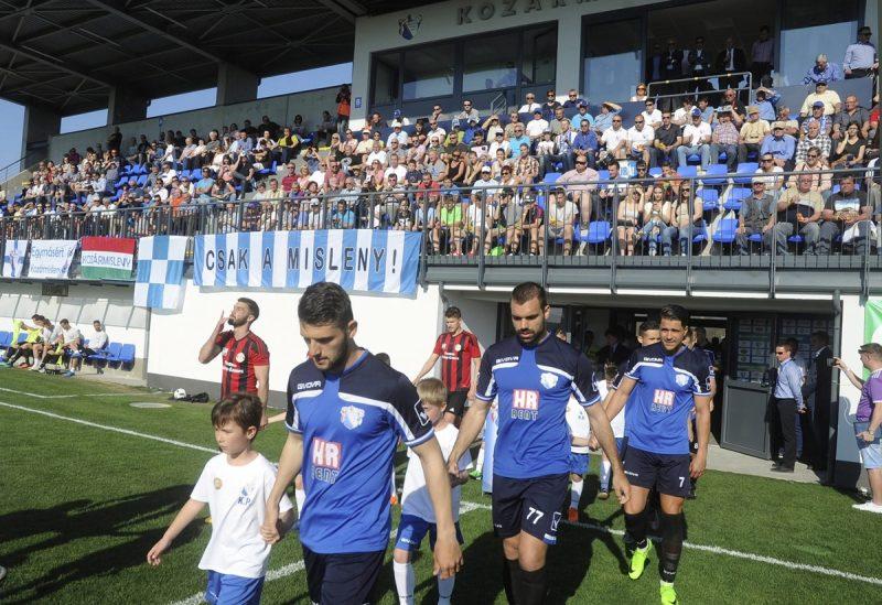 Kozármisleny, 2017. április 2. HR-Rent Kozármisleny (kékben) és a Dorog játékosai a pályára vonulnak a felújított kozármislenyi futballstadiont avatásán 2017. április 2-án. MTI Fotó: Lendvai Péter