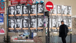 "This picture taken in Paris on April 19, 2017, shows posters of French presidential election candidates as part of a campaign of ""Solidarite Sida"". / AFP PHOTO / JOEL SAGET"