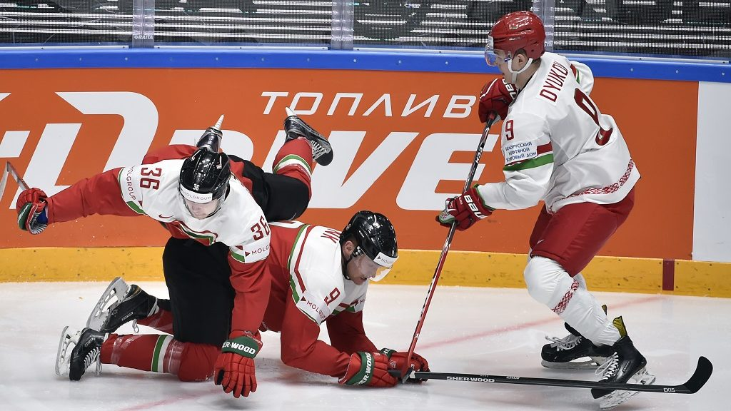 Hungary's forward Csanad Erdely flips over Hungary's forward Andras Benk next to Belarus' defender Roman Dyukov (R) during the group B preliminary round game Hungary vs Belarus at the 2016 IIHF Ice Hockey World Championship in Saint Petersburg on May 14, 2016. / AFP PHOTO / ALEXANDER NEMENOV