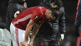 Manchester United's Swedish striker Zlatan Ibrahimovic is escorted from the pitch after getting injured during the UEFA Europa League quarter-final second leg football match between Manchester United and Anderlecht at Old Trafford in Manchester, north west England, on April 20, 2017. / AFP PHOTO / Oli SCARFF