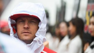 Ferrari's Finnish driver Kimi Raikkonen greets fans during the drivers' parade before the Formula One Chinese Grand Prix in Shanghai on April 9, 2017. / AFP PHOTO / Johannes EISELE