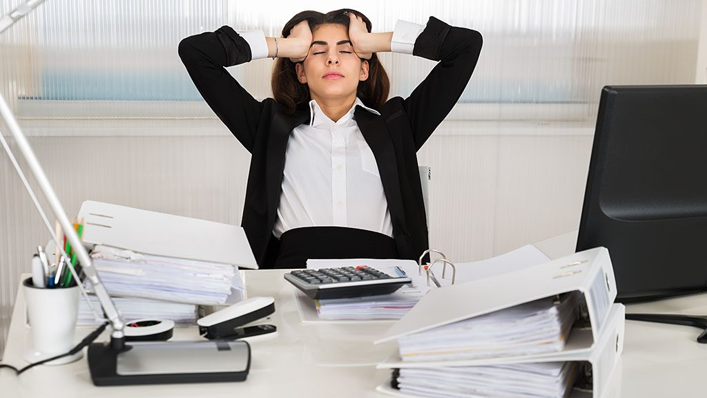 Tensed female accountant sitting with head in hands at desk in office