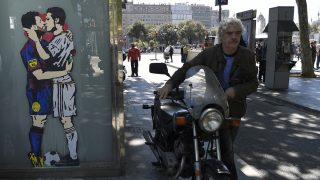 """A man pushes a motorbike past a street art """"Love is blind"""" of by artist Salva """"Tvboy"""" on April 21, 2017 in Barcelona, which shows Barcelona's Argentinian forward Lionel Messi and Real Madrid's Portuguese forward Cristiano Ronaldo kissing each other two days before 'El Clásico' match between Real Madrid and FC Barcelona. / AFP PHOTO / LLUIS GENE"""