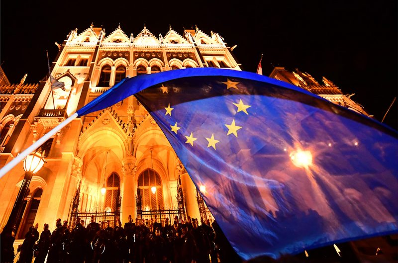 An EU flag is waved by a student as thousands of people protest against Hungarian Prime Minister Viktor Orban (not pictured) in front of the parliament building on April 12, 2017.An EU-flag is waved by a student as thousands of participants protest against Hungarian Prime Minister Viktor Orban (not pictured) in front of the parliament building on April 10, 2017 during their anti-government demonstration. / AFP PHOTO / ATTILA KISBENEDEK