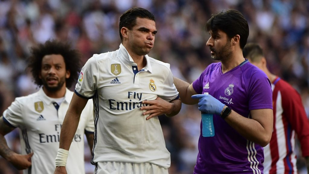 Real Madrid's Portuguese defender Pepe is assisted by a team member during the Spanish league football match Real Madrid CF vs Club Atletico de Madrid at the Santiago Bernabeu stadium in Madrid on April, 8, 2017. / AFP PHOTO / PIERRE-PHILIPPE MARCOU