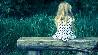 girl with long blond hair sitting in bench and waiting filtered effect back view