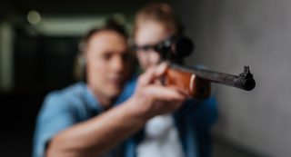 I am ready. Selective focus of a rifle being help by a clever young curious girl while standing with her father