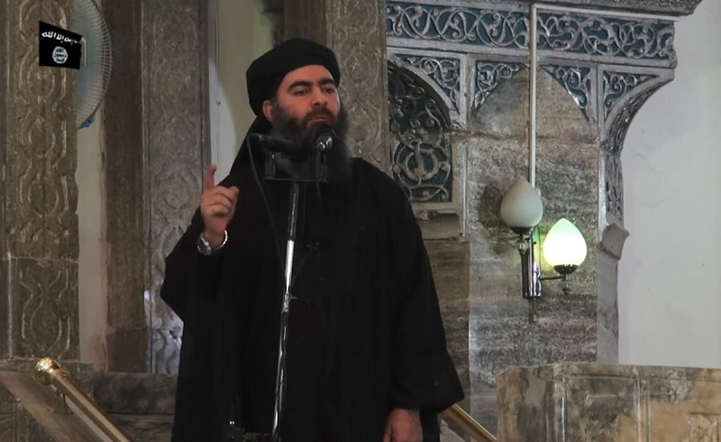 """This July 5, 2014 photo shows an image grab taken from a propaganda video released by al-Furqan Media allegedly showing the leader of the Islamic State (IS) jihadist group, Abu Bakr al-Baghdadi, aka Caliph Ibrahim, adressing Muslim worshippers at a mosque in the militant-held northern Iraqi city of Mosul. Baghdadi, who on June 29 proclaimed a """"caliphate"""" straddling Syria and Iraq, purportedly ordered all Muslims to obey him in the video released on social media.  In early 2014 the self-styled Islamic State entered the northern Syrian city of Raqqa, declaring it their capital and beginning a reign of terror marked by grisly public executions.Armed sharia police patrolled the streets as """"enemies"""" of the regime were crucified or decapitated, their severed heads impaled on spikes in the city square.Student Abdalaziz Alhamza and his friends decided to form """"Raqqa is Being Silently Slaughtered"""" (RBSS), a band of courageous citizen journalists who risk their lives to document IS atrocities. / AFP PHOTO / -"""