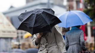 people with umbrellas walking in the city while it is heavy raining