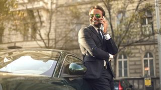 Elegant rich man in a suit leaning on his parked car while talking on the phone