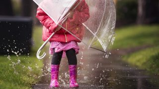 A young girl is playing in the much needed California rain.