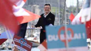 French presidential election candidate for the far-left coalition La France insoumise Jean-Luc Melenchon smiles during a public meeting at the Old Port of Marseille, southern France, on April 9, 2017. / AFP PHOTO / Anne-Christine POUJOULAT