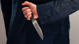 Cropped shot of senior businessman in suit with knife behind back. Business betray concept.