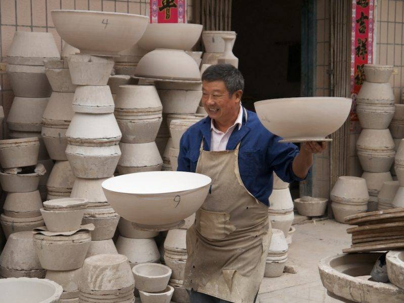 Carrying two eggshell bowls with freshly-glazed interiors in the Old Factory, Jingdezhen
