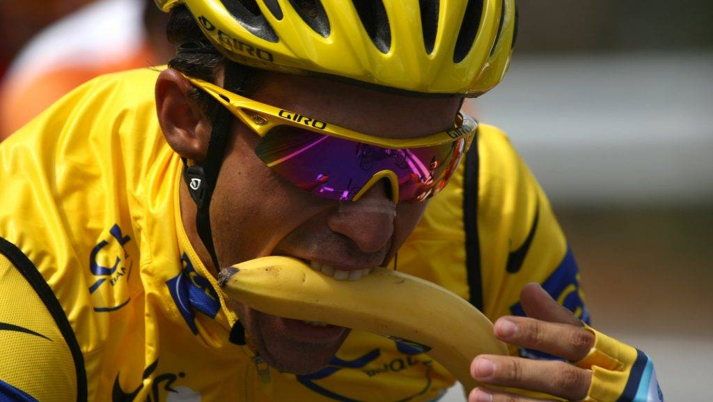 2007 Tour de France winner and Kazakh cycling team Astana (AST)'s leader Alberto Contador of Spain bites a banana as he rides in the pack on July 21, 2009 during the 159 km and sixteenth stage of the 2009 Tour de France cycling race run between Martigny and Bourg Saint-Maurice. Spanish cycling team Euskatel-Euskadi (Eus)'s Mikel Astarloza of Spain won the stage ahead of French cycling team Francaise des Jeux (FDJ)'s leader Sandy Casar of France and French cycling team BBOX Bouygues Telecom (BBO)'s Pierrick Fedrigo of France.  AFP PHOTO JOEL SAGET / AFP PHOTO / JOEL SAGET