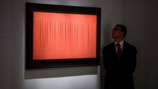 """A security member looks at Lucio Fontana's 'Concetto Spaziale, Attese at """"The Loaded Brush"""" display by auction house Christie's in Hong Kong on November 23, 2016. Auction house Christie's is holding its first ever sale of Western art masterpieces in Hong Kong this week, in response to a surge in interest from wealthy Asian collectors.    / AFP PHOTO / Anthony WALLACE / RESTRICTED TO EDITORIAL USE - MANDATORY MENTION OF THE ARTIST UPON PUBLICATION - TO ILLUSTRATE THE EVENT AS SPECIFIED IN THE CAPTION"""