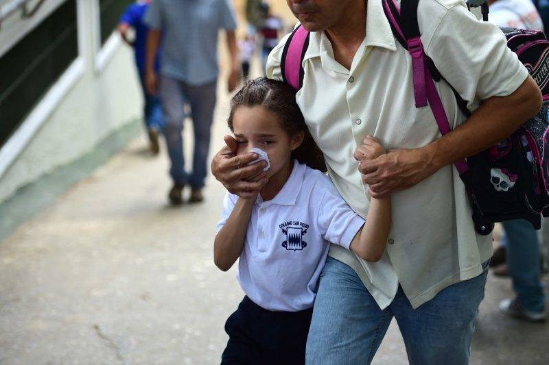 A schoolgirl covers her nose and mouth to avoid breathing tear gas shot by police at opponents of Venezuelan President Nicolas Maduro marching in Caracas on April 26, 2017.Protesters in Venezuela plan a high-risk march against President Maduro Wednesday, sparking fears of fresh violence after demonstrations that have left 26 dead in the crisis-wracked country. / AFP PHOTO / RONALDO SCHEMIDT