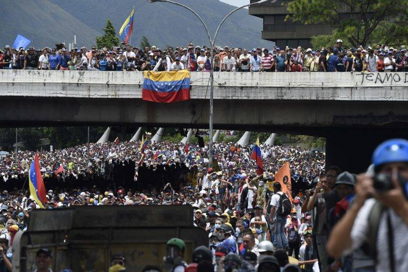 Opposition activists march during a protest against Venezuelan President Nicolas Maduro, in Caracas on May 3, 2017.Venezuela's angry opposition rallied Wednesday vowing huge street protests against President Nicolas Maduro's plan to rewrite the constitution and accusing him of dodging elections to cling to power despite deadly unrest. / AFP PHOTO / JUAN BARRETO