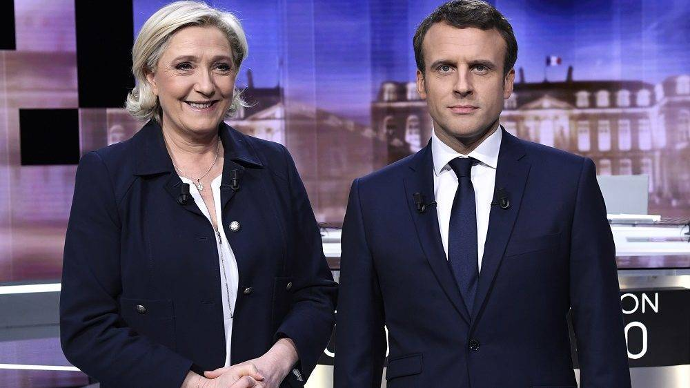 French presidential election candidate for the far-right Front National (FN) party, Marine Le Pen (L) and French presidential election candidate for the En Marche ! movement, Emmanuel Macron pose prior to the start of a live brodcast face-to-face televised debate in television studios of French public national television channel France 2, and French private channel TF1 in La Plaine-Saint-Denis, north of Paris, on May 3, 2017 as part of the second round election campaign. Pro-EU centrist Emmanuel Macron and far-right leader Marine Le Pen face off in a final televised debate on May 3 that will showcase their starkly different visions of France's future ahead of this weekend's presidential election run-off.  / AFP PHOTO / POOL / Eric FEFERBERG / ALTERNATIVE CROP