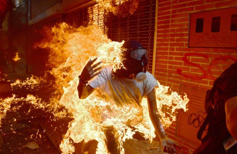 A demonstrator catches fire during clashes with riot police within a protest against Venezuelan President Nicolas Maduro, in Caracas on May 3, 2017.Venezuela's angry opposition rallied Wednesday vowing huge street protests against President Nicolas Maduro's plan to rewrite the constitution and accusing him of dodging elections to cling to power despite deadly unrest. / AFP PHOTO / RONALDO SCHEMIDT