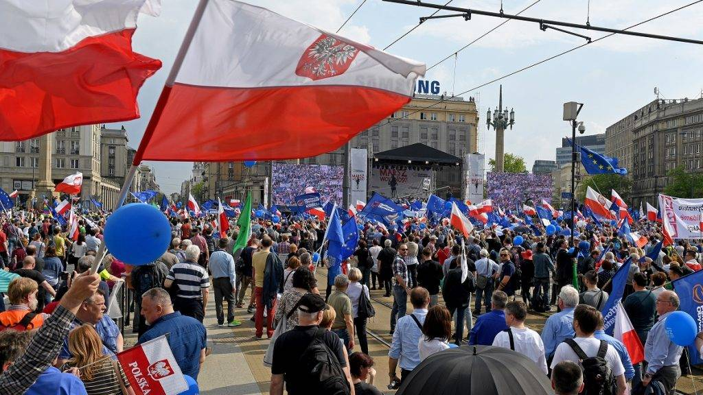 """Demonstrators hold Polish and EU flags during the """"Freedom March"""" in the Polish capital Warsaw on May 6, 2017 organised by Poland's main liberal Civic Platform (PO) opposition party to protest against the rightwing nationalist Law and Justice (PiS) government over alleged rule of law violations. / AFP PHOTO / Janek SKARZYNSKI"""