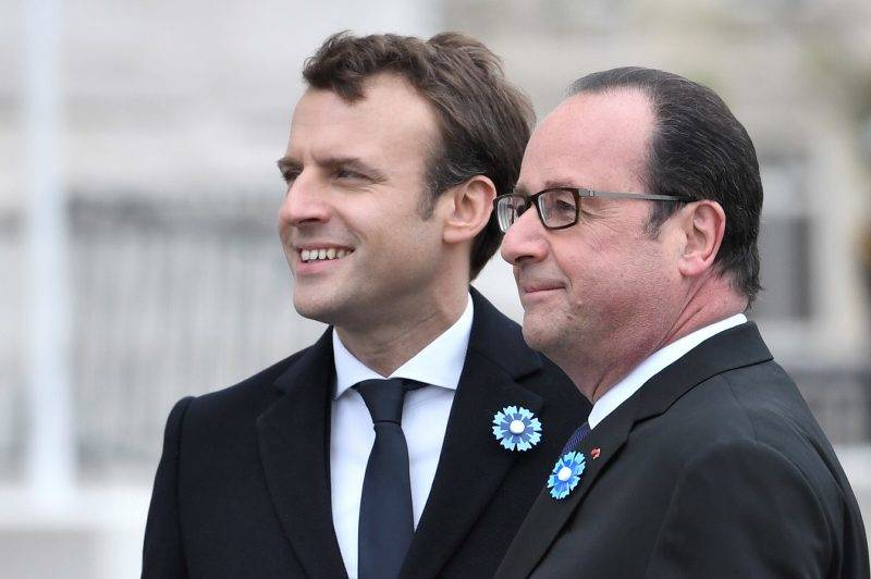 Outgoing French president Francois Hollande (R) and French president-elect Emmanuel Macron hug during the ceremony marking the 72nd anniversary of the victory over Nazi Germany during WWII on May 8, 1945 under the Arc de Triomphe monument in Paris on May 8, 2017. / AFP PHOTO / POOL / STEPHANE DE SAKUTIN / ALTERNATIVE CROP