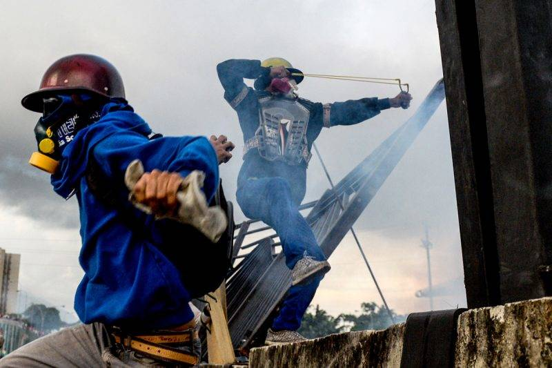 """Opposition activists and riot police clash during a protest against President Nicolas Maduro, in Caracas on May 8, 2017.Venezuela's opposition mobilized Monday in fresh street protests against President Nicolas Maduro's efforts to reform the constitution in a deadly political crisis. Supporters of the opposition Democratic Unity Roundtable (MUD) gathered in eastern Caracas to march to the education ministry under the slogan """"No to the dictatorship."""" / AFP PHOTO / FEDERICO PARRA"""