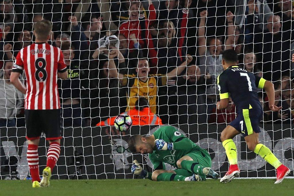 Arsenal's Chilean striker Alexis Sanchez (R) scores the opening game past Southampton's English goalkeeper Fraser Forster during the English Premier League football match between Southampton and Arsenal at St Mary's Stadium in Southampton, southern England on May 10, 2017. / AFP PHOTO / Adrian DENNIS / RESTRICTED TO EDITORIAL USE. No use with unauthorized audio, video, data, fixture lists, club/league logos or 'live' services. Online in-match use limited to 75 images, no video emulation. No use in betting, games or single club/league/player publications.  /