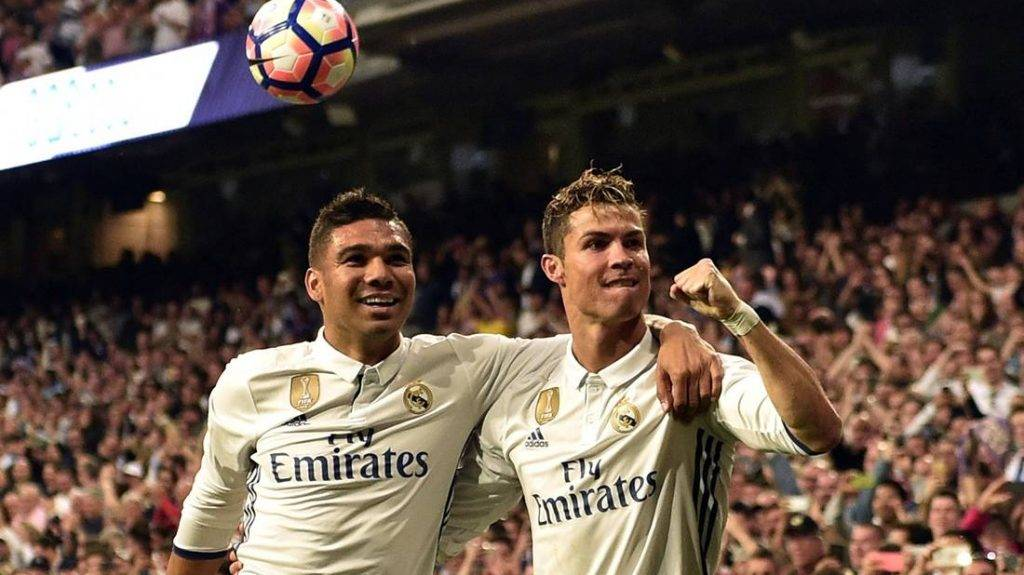 Real Madrid's Portuguese forward Cristiano Ronaldo (R) celebrates a goal with Real Madrid's Brazilian midfielder Casemiro during the Spanish league football match Real Madrid CF vs Sevilla FC at the Santiago Bernabeu stadium in Madrid on May 14, 2017. / AFP PHOTO / GERARD JULIEN