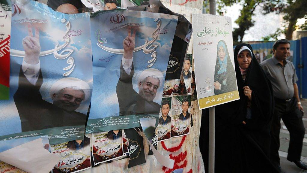 Iranians walk by a wall plastered with election posters of President and candidate Hassan Rouhani on a street in the capital Tehran on May 17, 2017.