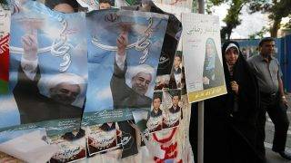 Iranians walk by a wall plastered with election posters of President and candidate Hassan Rouhani on a street in the capital Tehran on May 17, 2017.Iran's presidential election on May 19 is effectively a choice between moderate incumbent Hassan Rouhani and hardline jurist Ebrahim Raisi, with major implications for everything from civil rights to relations with Washington. / AFP PHOTO / ATTA KENARE