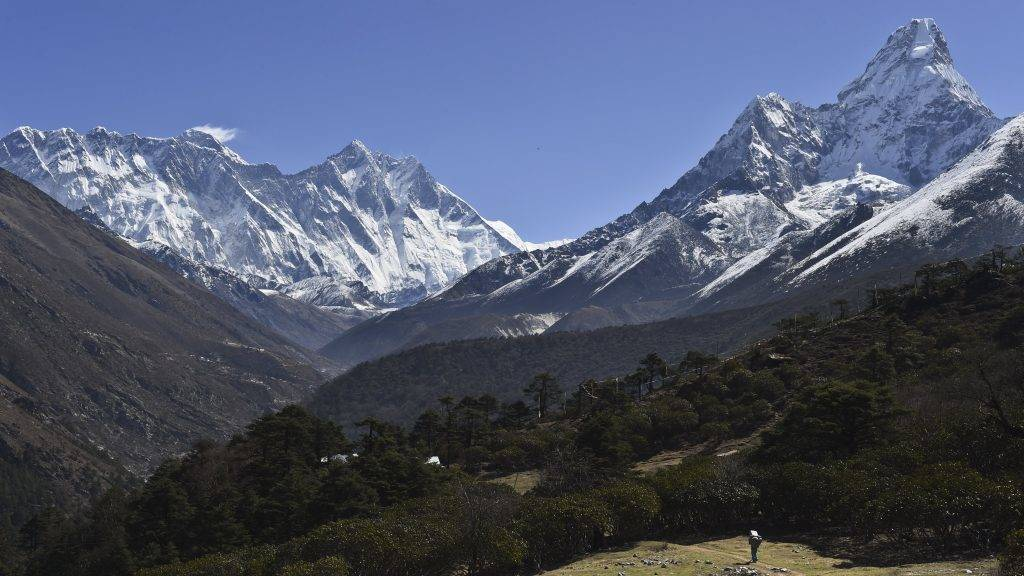 "(FILES) In this photograph taken on April 20, 2015, a Nepalese porter carries goods along a pathway in the Himalayas, with Mount Everest on the left, in the village of Tembuche in the Khumbu region of northeastern Nepal. An American climber died May 21, 2017 on his way to the summit of Mount Everest, expedition organisers said, the latest death to mar the ongoing climbing season. The 50-year-old mountaineer died close to the Balcony, a small platform above the 8,000-metre mark considered the mountain's ""death zone"". / AFP PHOTO / ROBERTO SCHMIDT"