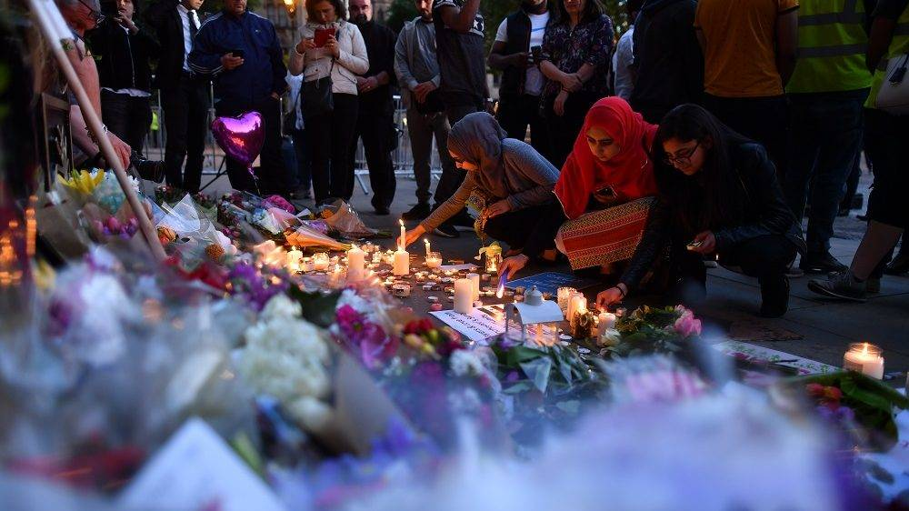 People light candles in front of  messages and floral tributes in Albert Square in Manchester, northwest England on May 23, 2017, in solidarity with those killed and injured in the May 22 terror attack at the Ariana Grande concert at the Manchester Arena. Twenty two people have been killed and dozens injured in Britain's deadliest terror attack in over a decade after a suspected suicide bomber targeted fans leaving a concert of US singer Ariana Grande in Manchester. British police on Tuesday named the suspected attacker behind the Manchester concert bombing as Salman Abedi, but declined to give any further details. / AFP PHOTO / Ben STANSALL