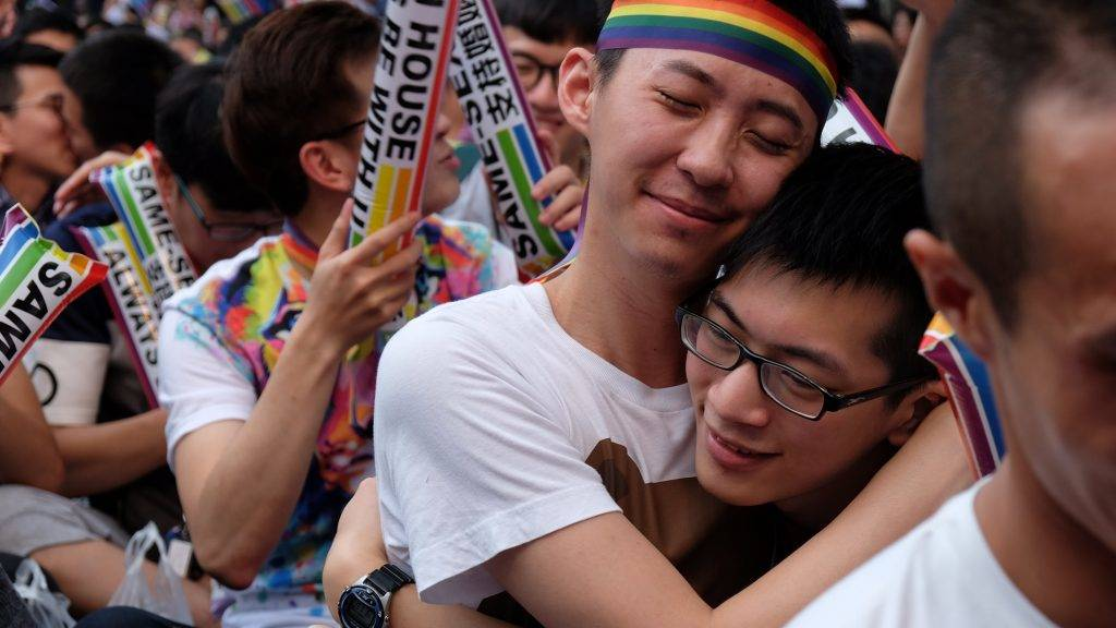 Same-sex activists hug outside the parliament in Taipei on May 24, 2017 as they celebrate the landmark decision paving the way for the island to become the first place in Asia to legalise gay marriage. Crowds of pro-gay marriage supporters in Taiwan on May 24 cheered, hugged and wept as a top court ruled in favour of same-sex unions. / AFP PHOTO / SAM YEH