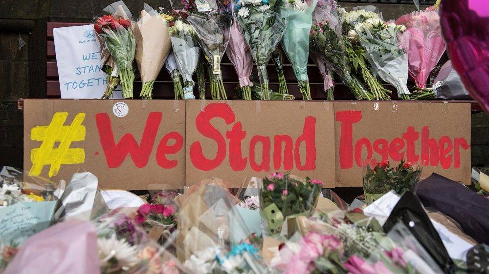 """Floral tributes and a message that reads """"We Stand Together"""" are pictured in Albert Square in Manchester, northwest England on May 24, 2017, left as tributes to the victims of the May 22 terror attack at the Manchester Arena. Police on Tuesday named Salman Abedi -- reportedly British-born of Libyan descent -- as the suspect behind a suicide bombing that ripped into young fans at an Ariana Grande concert at the Manchester Arena on May 22, as the Islamic State group claimed responsibility for the carnage. / AFP PHOTO / CHRIS J RATCLIFFE"""