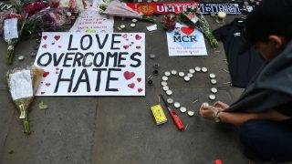 A man makes a heart-shape out of candles alongside flowers and messages in Albert Square in Manchester, northwest England on May 24, 2017, placed in tribute to the victims of the May 22 terror attack at the Manchester Arena. Police on Tuesday named Salman Abedi -- reportedly British-born of Libyan descent -- as the suspect behind a suicide bombing that ripped into young fans at an Ariana Grande concert at the Manchester Arena on May 22, as the Islamic State group claimed responsibility for the carnage. / AFP PHOTO / Ben STANSALL