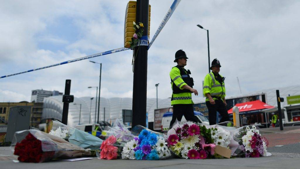 Police officers pass flowers laid by a cordon, close to Manchester Arena and Victoria Station in Manchester, northwest England on May 24, 2017, following the May 22 terror attack at the Manchester Arena. Police on Tuesday named Salman Abedi -- reportedly British-born of Libyan descent -- as the suspect behind a suicide bombing that ripped into young fans at an Ariana Grande concert at the Manchester Arena on May 22, as the Islamic State group claimed responsibility for the carnage. / AFP PHOTO / Ben STANSALL