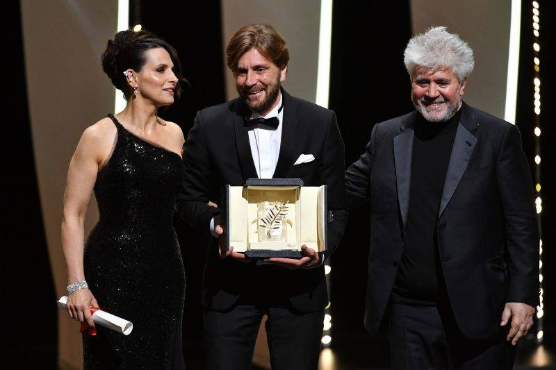 Swedish director Ruben Ostlund (C) poses on stage with French actress Juliette Binoche (L) and Spanish director and President of the Feature Film Jury Pedro Almodovar after he was awarded with the Palme d'Or for the film 'The Square' on May 28, 2017 during the closing ceremony of the 70th edition of the Cannes Film Festival in Cannes, southern France.  / AFP PHOTO / Alberto PIZZOLI