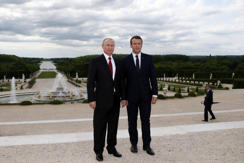 French President Emmanuel Macron (R), and his Russian counterpart Vladimir Putin pose in the garden of the  Palace of Versailles following their meeting in Versailles, near Paris, on May 29, 2017.  Macron hosts Russian counterpart Vladimir Putin in their first meeting since he came to office with differences on Ukraine and Syria clearly visible. / AFP PHOTO / POOL / Francois Mori