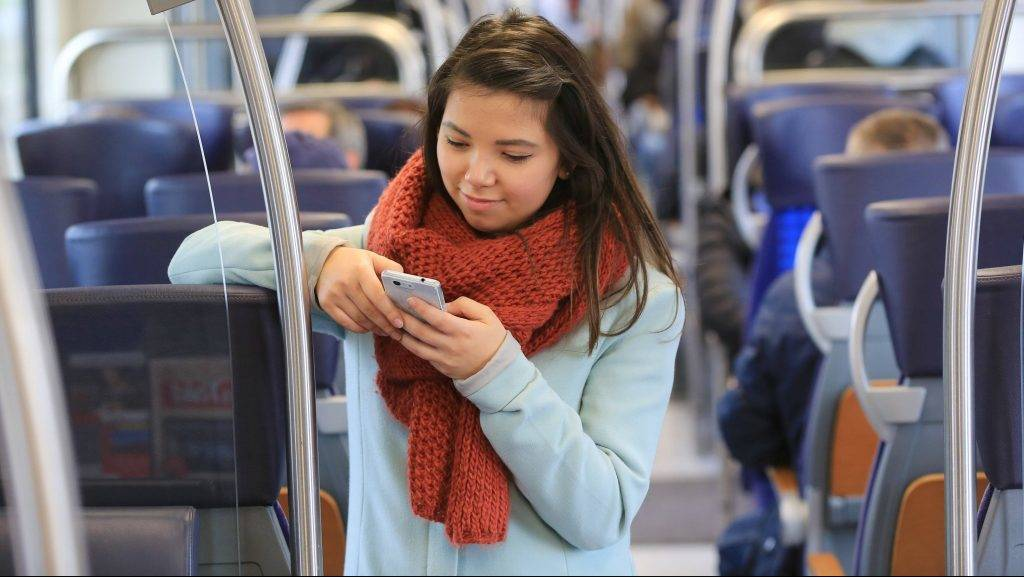 A young woman surfs the internet on her smartphone on a regional train on the line between Magdbeurg and Schoenebeck, Germany, 5 April 2017. Passangers on many regional trains will now be able to make use of a free Wi-Fi connection. Photo: Peter Gercke/dpa-Zentralbild/dpa