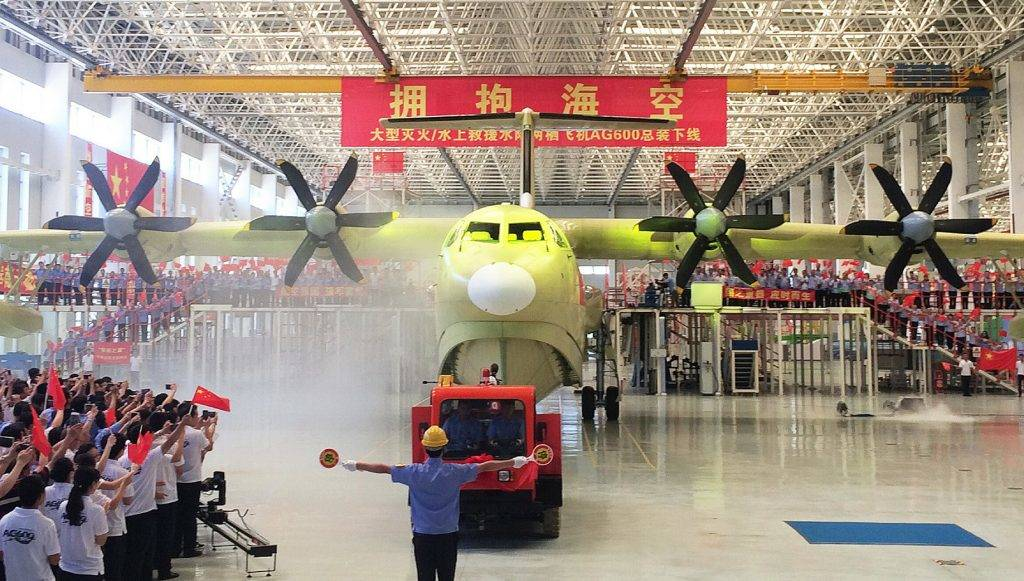 This picture taken on July 23, 2016 shows a crowd waving flags during a ceremony to unveil the AG600 amphibious plane in Zhuhai, in south China's Guangdong Province.   China has completed production of the world's largest amphibious aircraft, state media has said, the latest effort in the country's program to wean itself off dependence on foreign aviation firms. / AFP PHOTO / STR / China OUT