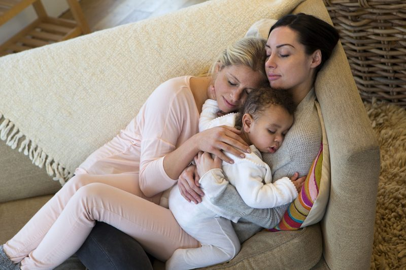 Same sex female couple sleeping with their baby son on their sofa at home