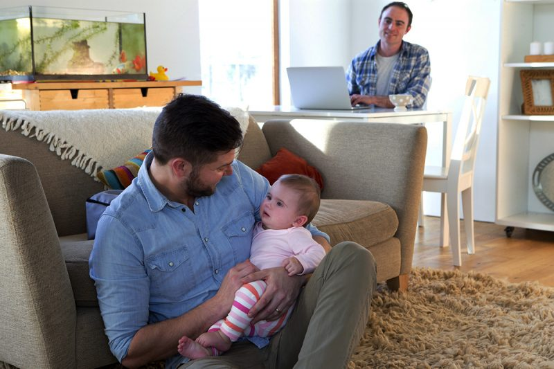 Same sex male couple sitting in their home. One father is sitting on the floor with their daughter in his arms.